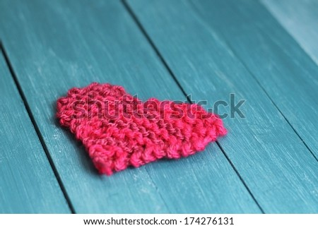 handmade pink knitted heart shape on blue wooden boards , shabby chic valentine gift, shallow depth of field  - stock photo