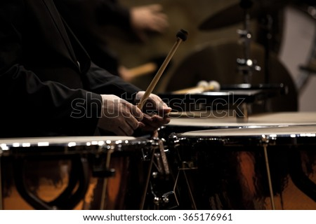 Hands musician playing timpani in dark colors closeup