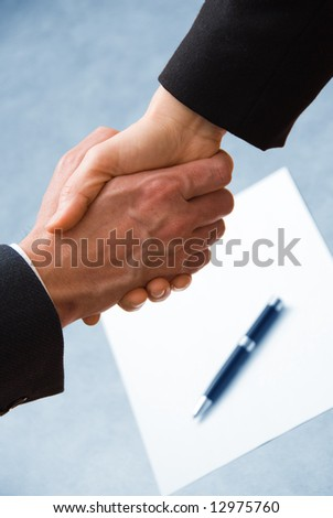 2 hands shaking with a blank contract and pen - stock photo
