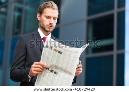 handsome businessman holding a newspaper