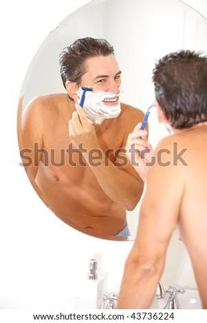 handsome man shaving in the bathroom - stock photo