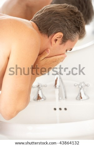 handsome man washing in the bathroom - stock photo