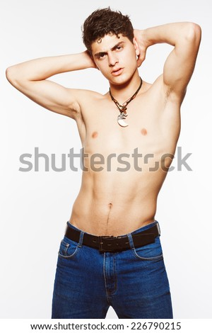 Handsome muscular male model with ethnic leather necklaces over white background with hands up.