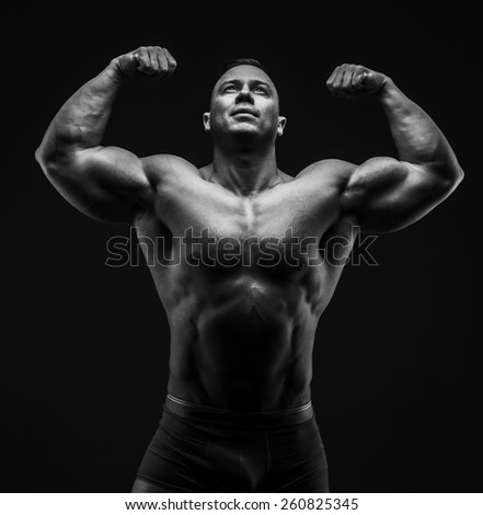 Handsome power athletic guy posing in studio. Black and white - stock photo