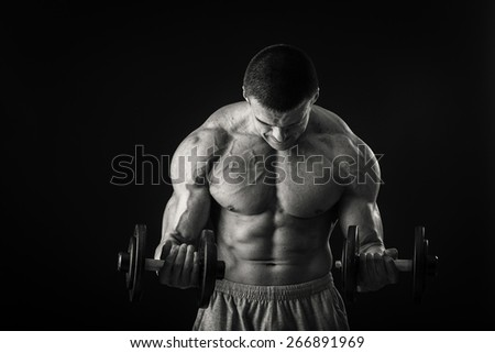 Handsome strong man with beautiful body in sport wear with dumbbell in hand isolated ob black background - stock photo
