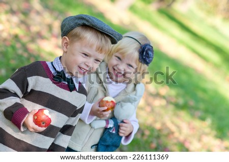 Happiness children eat apples outdoors - stock photo