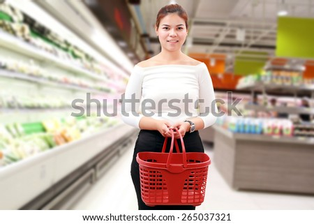 happiness, consumerism, sale and people concept - smiling young woman Asian with shopping basket and buy vegetable/fruit at supermarket/mall  - stock photo