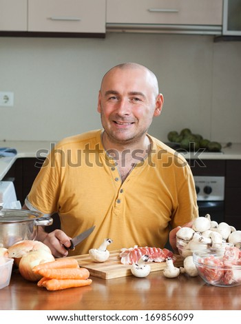 Happy adult man prepares a dish of meat - stock photo