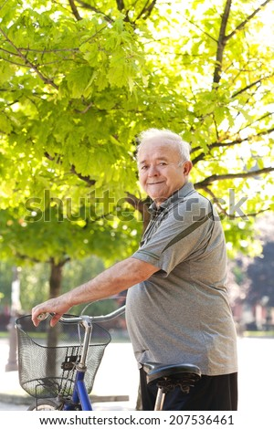 happy and smiling elderly man with bike - stock photo