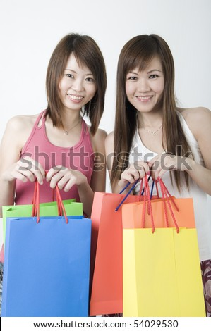 2 happy asian girls smiling with shopping bags - stock photo
