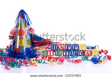 """Happy Birthday"" blocks on a white background with copy space, including a party hat and streamers."