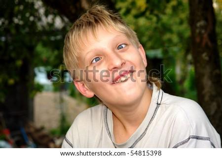 Happy boy builds smileys in the garden under the apple tree - stock photo