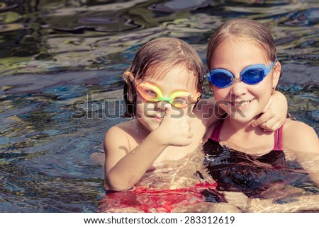 happy children  playing on the swimming pool at the day time - stock photo