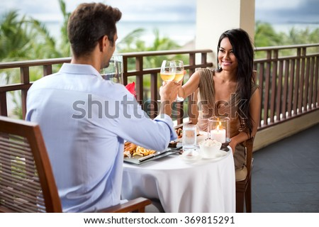 Happy couple toasting during romantic dinner on the balcony - stock photo