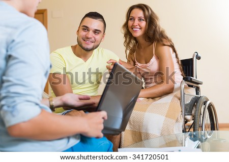 Happy couple with disabled woman talking with female agent