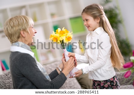 Happy cute girl giving flower her grandma on grandmother day - stock photo