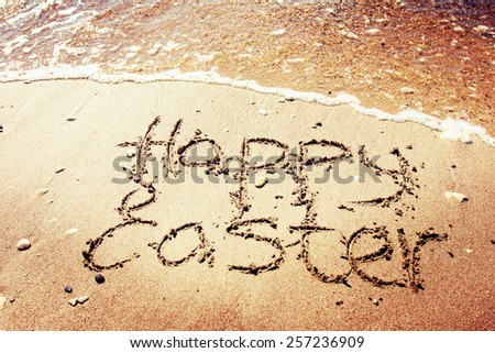 """Happy easter"" written in the sand on sea background - stock photo"