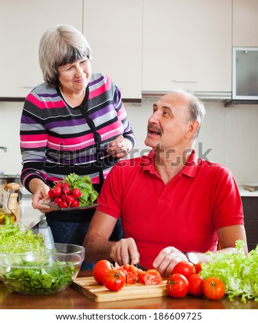 happy elderly couple cooking vegetables lunch in home kitchen