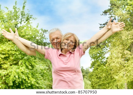 Happy elderly couple with raised arms outdoors.