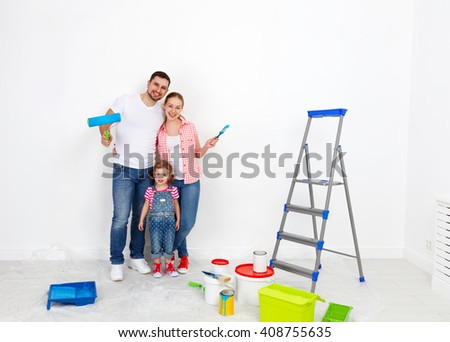 happy family mother father and child daughter are doing repairs paint wall at home - stock photo