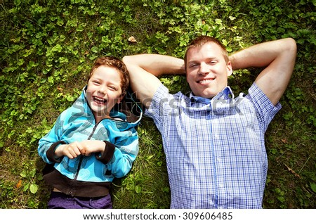 happy father and his son laying on the grass             - stock photo
