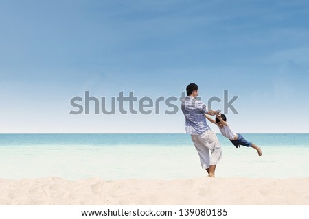 Happy father and son playing together at beach - stock photo