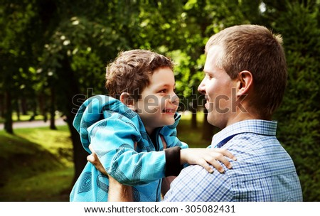 Happy father and son playing together, outdoors - stock photo