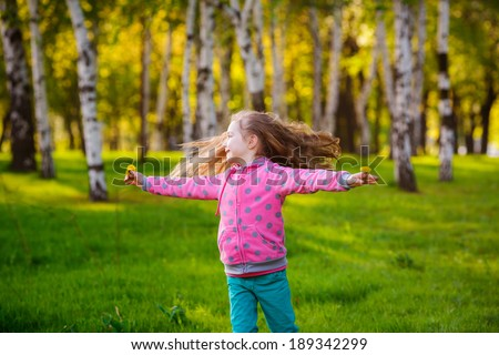 Happy girl running in the park. Wind blows hair. Happiness, smile, summer - stock photo