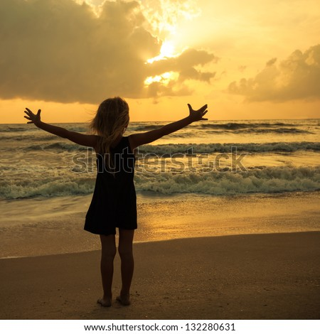 happy girl standing on the beach on the dawn time - stock photo