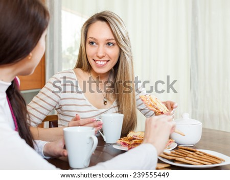 happy girls  drinking tea and gossiping in home - stock photo