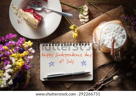 """Happy independence day 4th july"" is written on Notepad with pen, a glass of Thai tea and bits of red velvet cake on rustic wood background with low key scene"