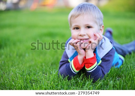 happy little boy lying on grass