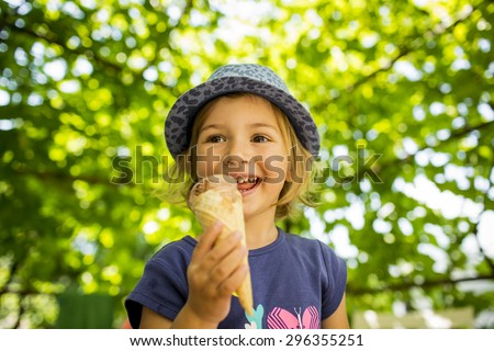 happy little girl licking ice cream in a cone - stock photo