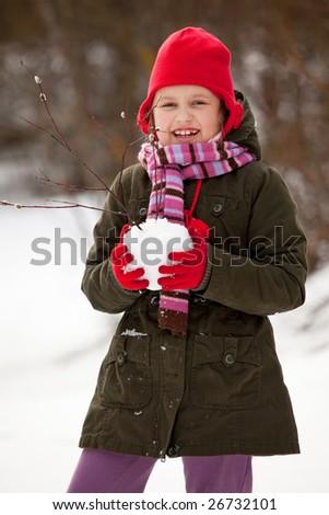 Happy little girl portrait, litle girl making snowballs - stock photo