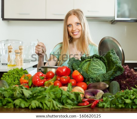 happy long-haired woman cooking with heap of raw vegetables in home kitchen - stock photo