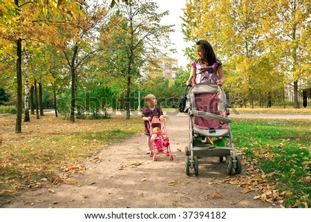 Happy mother with child  walking across city park - stock photo