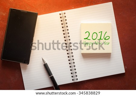 """2016 Happy new year"" is written on opened notepad with pen, small sticky paper and black smart phone on rustic cement background with low key scene. - stock photo"