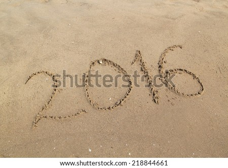 2016 happy new year written on sandy beach - stock photo
