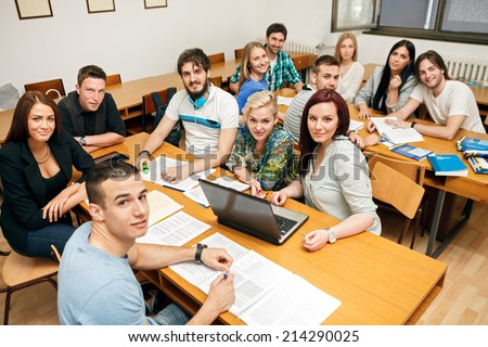 Happy students in a classroom in university class - stock photo