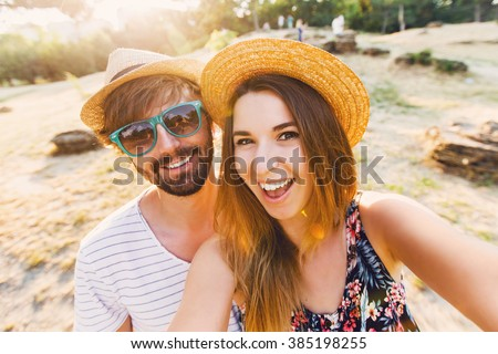 Happy traveling couple  making selfie  mountains  background , sunny summer colors, romantic mood. Stylish sunglasses, straw hat. Happy laughing  emotional faces.  - stock photo