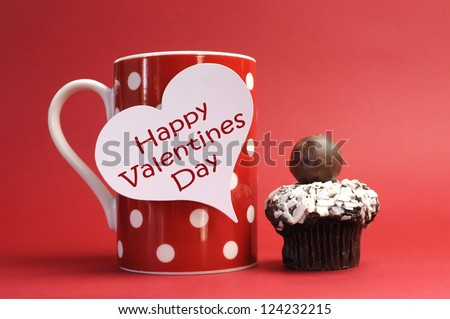 """""""Happy Valentines Day"""" messages on red polka dot mug with chocolate cupcake against a red background for a bright, fun and cheerful Valentines Day. - stock photo"""