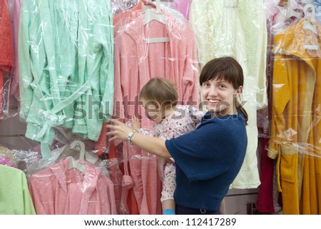 Happy woman and child chooses bathrobe at shop - stock photo