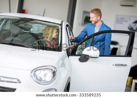 Happy woman buying car from car agent - stock photo