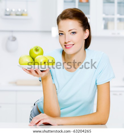 happy woman with green apples on a plate on kitchen