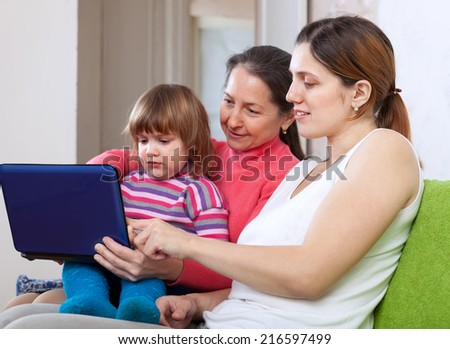 Happy women of three generations sits on sofa in livingroom with netbook  - stock photo