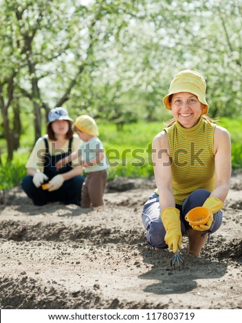 Happy women with child works at vegetables garden in spring