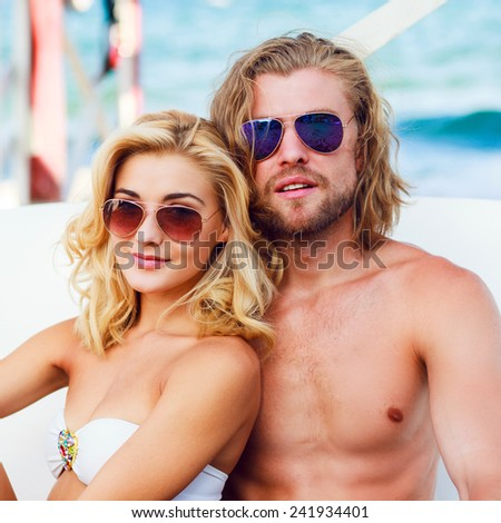 Happy young beach couple closeup portrait outdoors in sun. Young people wearing sunglasses eyewear. Athletic handsome man and young pretty woman smiling  and enjoy summer. - stock photo