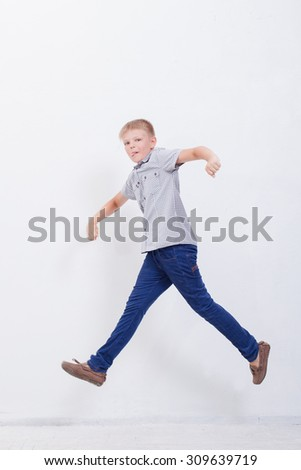 happy young boy jumping over a white background - stock photo