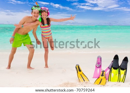 Happy young brother and sister playing in tropical beach with snorkels, flippers embedded in sand. - stock photo