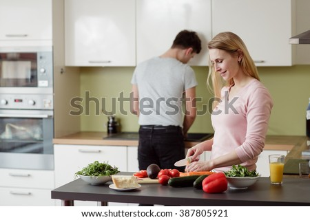 Happy young couple preparing salad in the kitchen at home. Young blond lady is cutting the carrot. - stock photo
